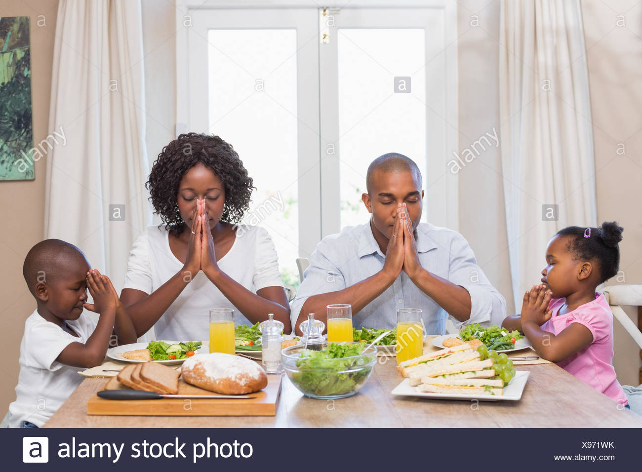 Happy family saying grace before meal - Stock Image