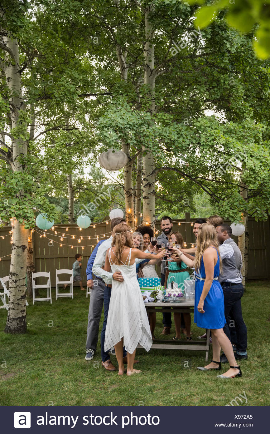 Bride, groom and wedding guests toasting wine reception - Stock Image