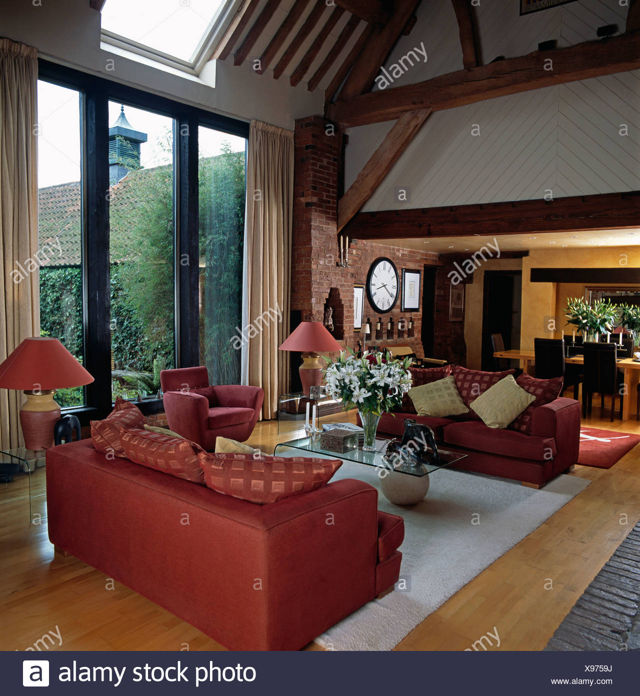 Red sofas and white rug in front of glass doors in living ...