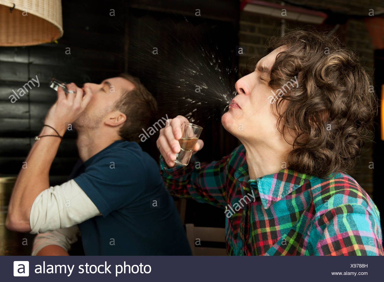 Two men drinking shots - Stock Image