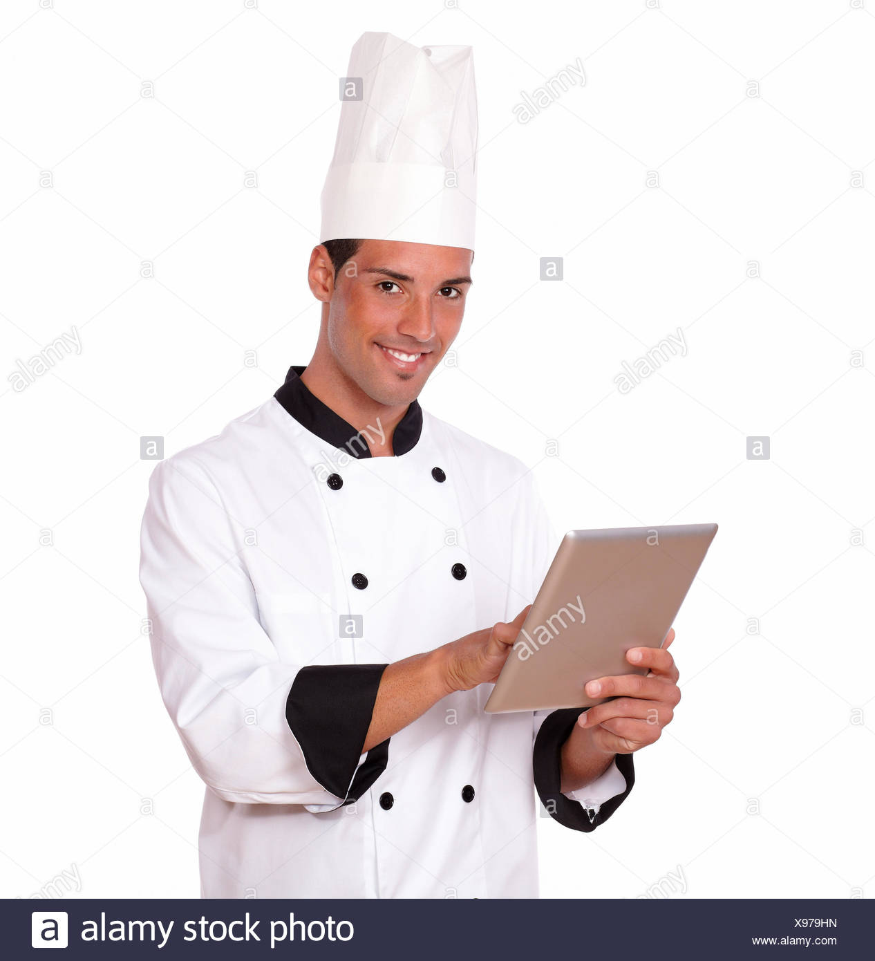 Portrait of professional 20s chef man on white uniform using his tablet pc while smiling at you on isolated studio. - Stock Image