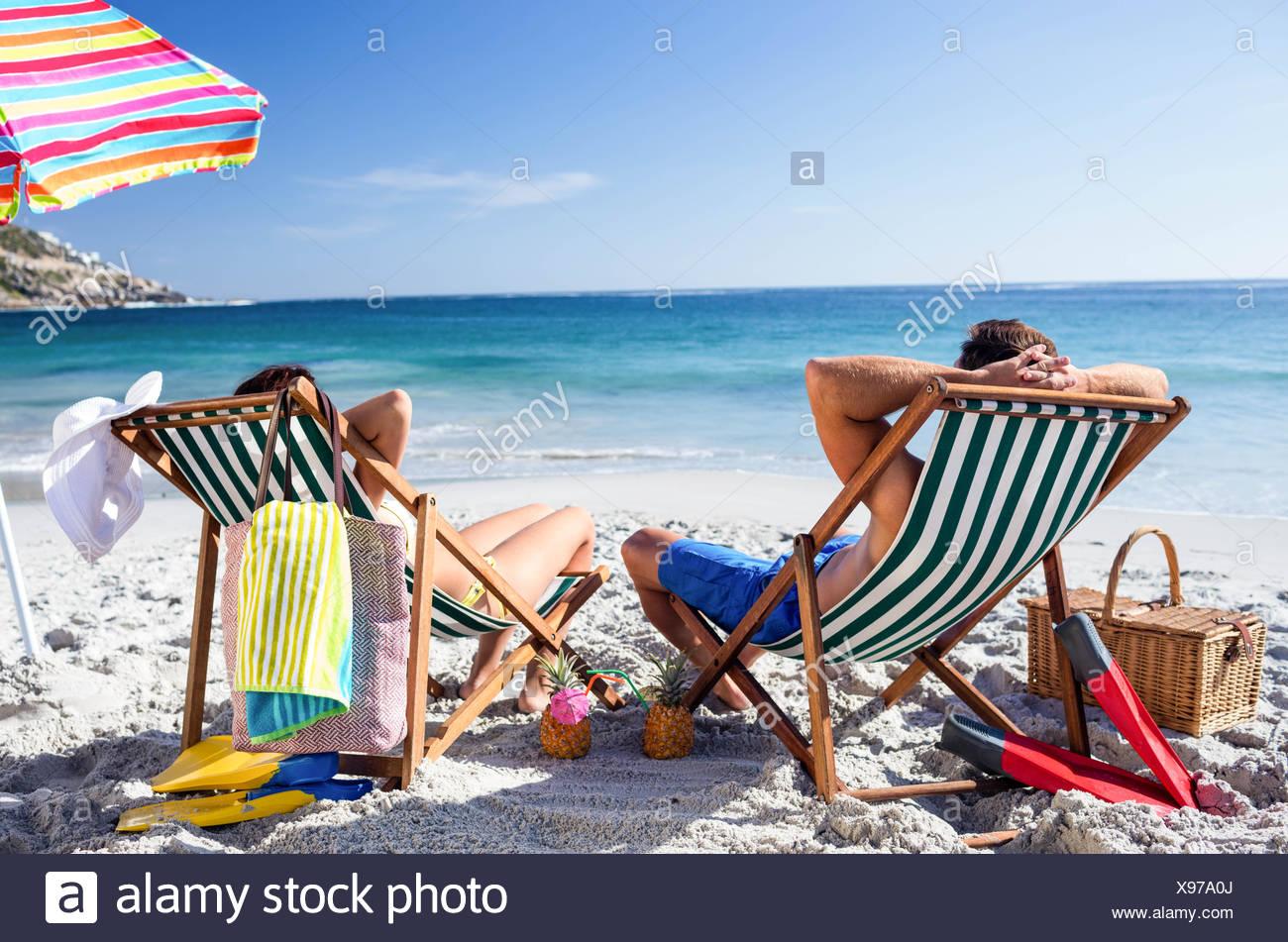 Cute couple lying on deckchairs Stock Photo