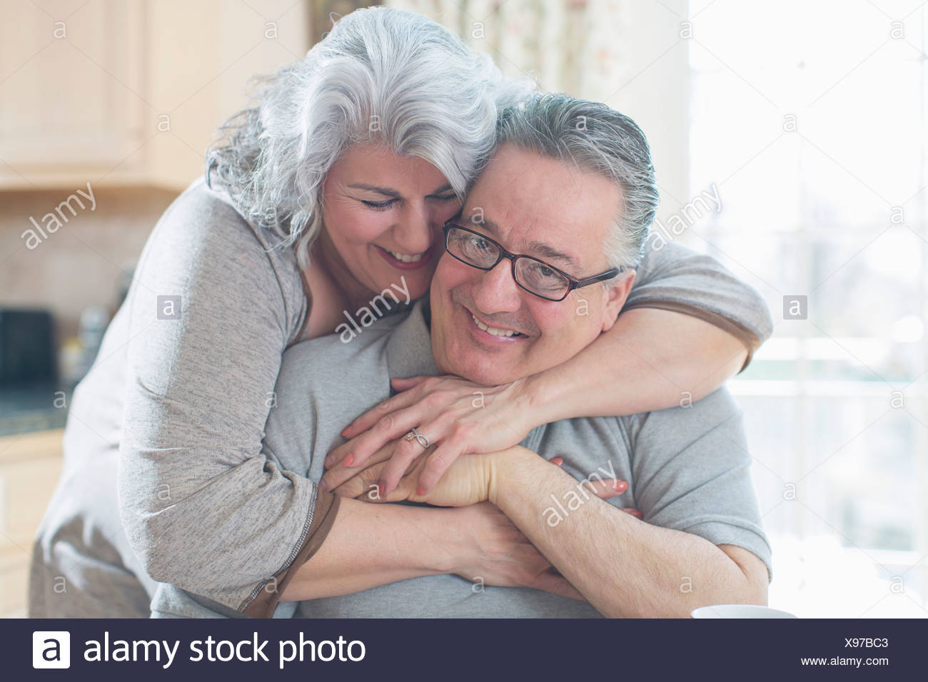Affectionate mature adult couple hugging at home - Stock Image