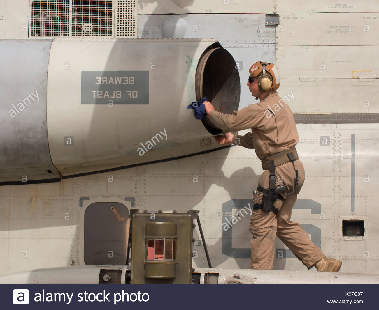 A US Marine Crew Chief Inspects Exhaust Jet Engine CH-53D