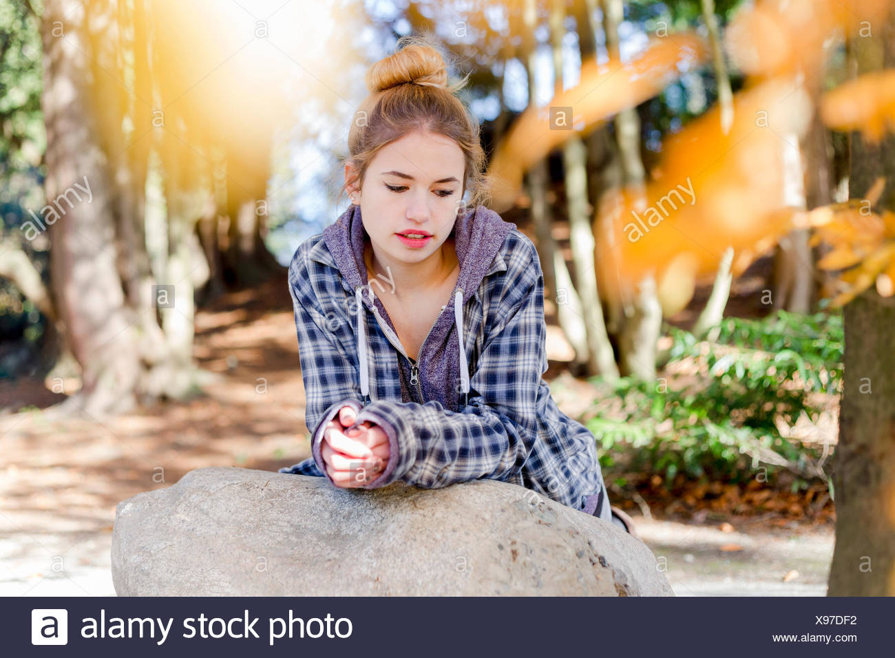 This young teenage girl hangs out alone in a park, sitting on a rock in a thoughtful disengaged position thinking to herself - Stock Image