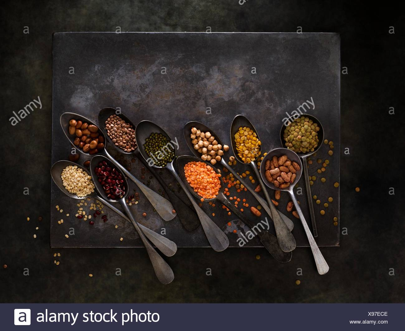 Pulses on metal spoons, overhead view. Stock Photo