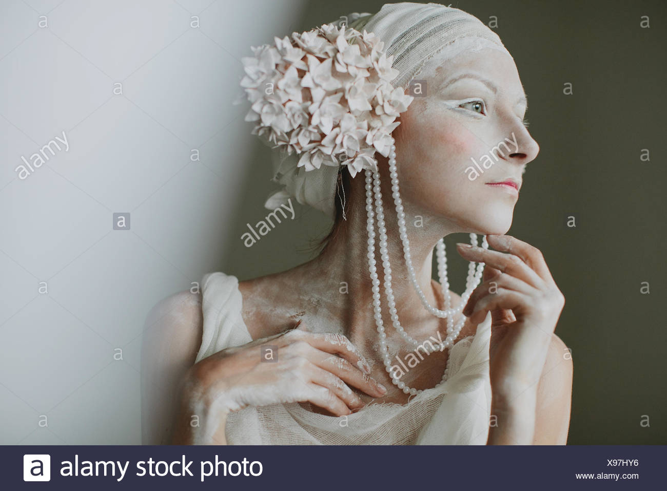 Portrait of young woman wearing make up, greasepaint, beads, and ear decorations resembling inflorescence - Stock Image