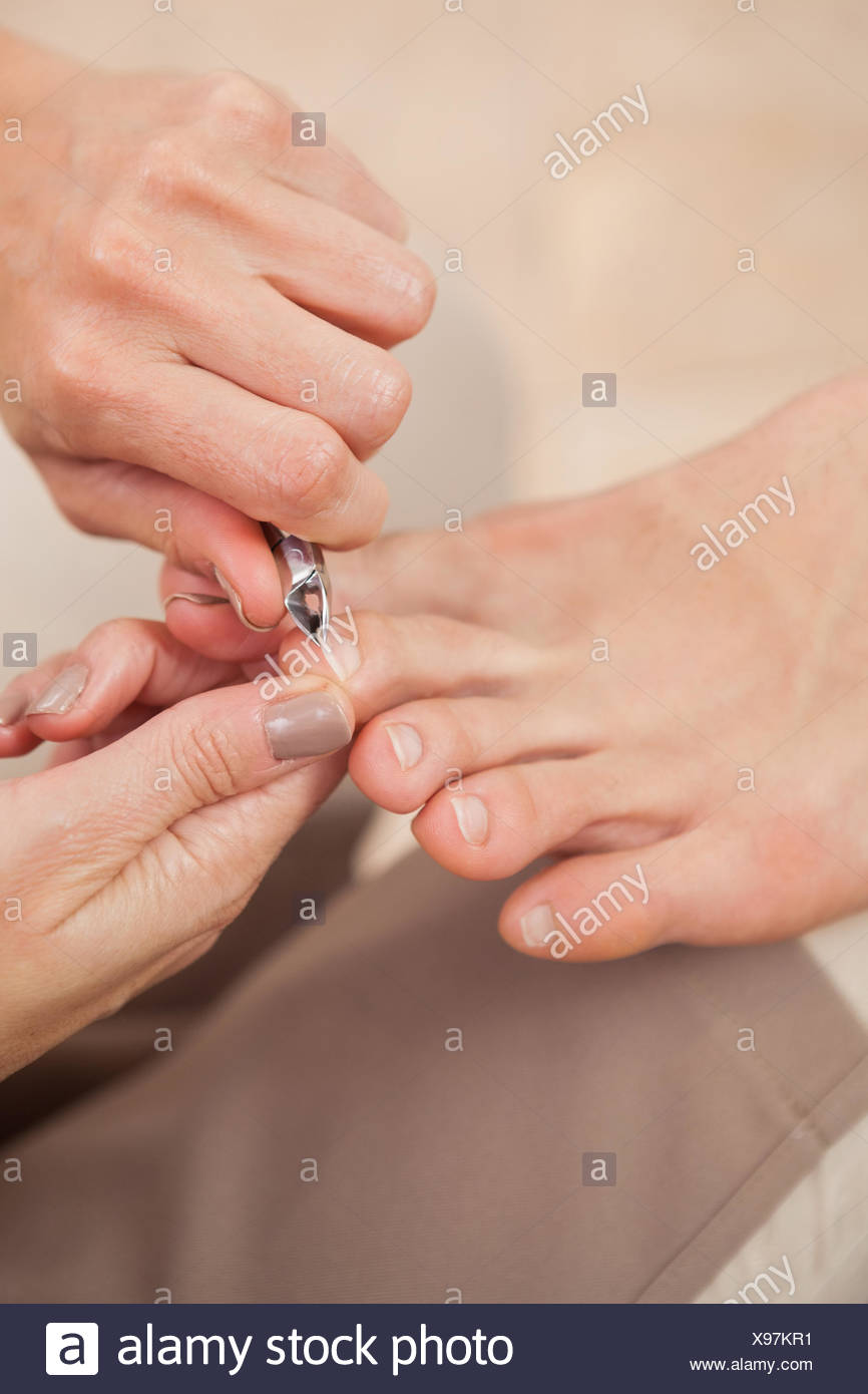 Pedicurist clipping customers toe nails - Stock Image