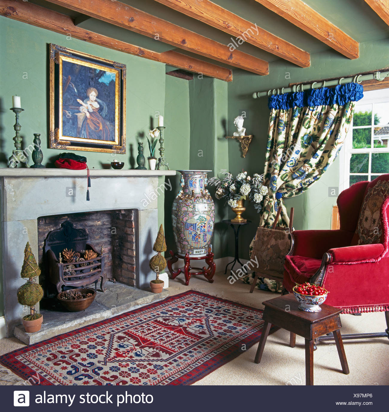 Tall Chinese pot beside fireplace in pale green cottage living room ...