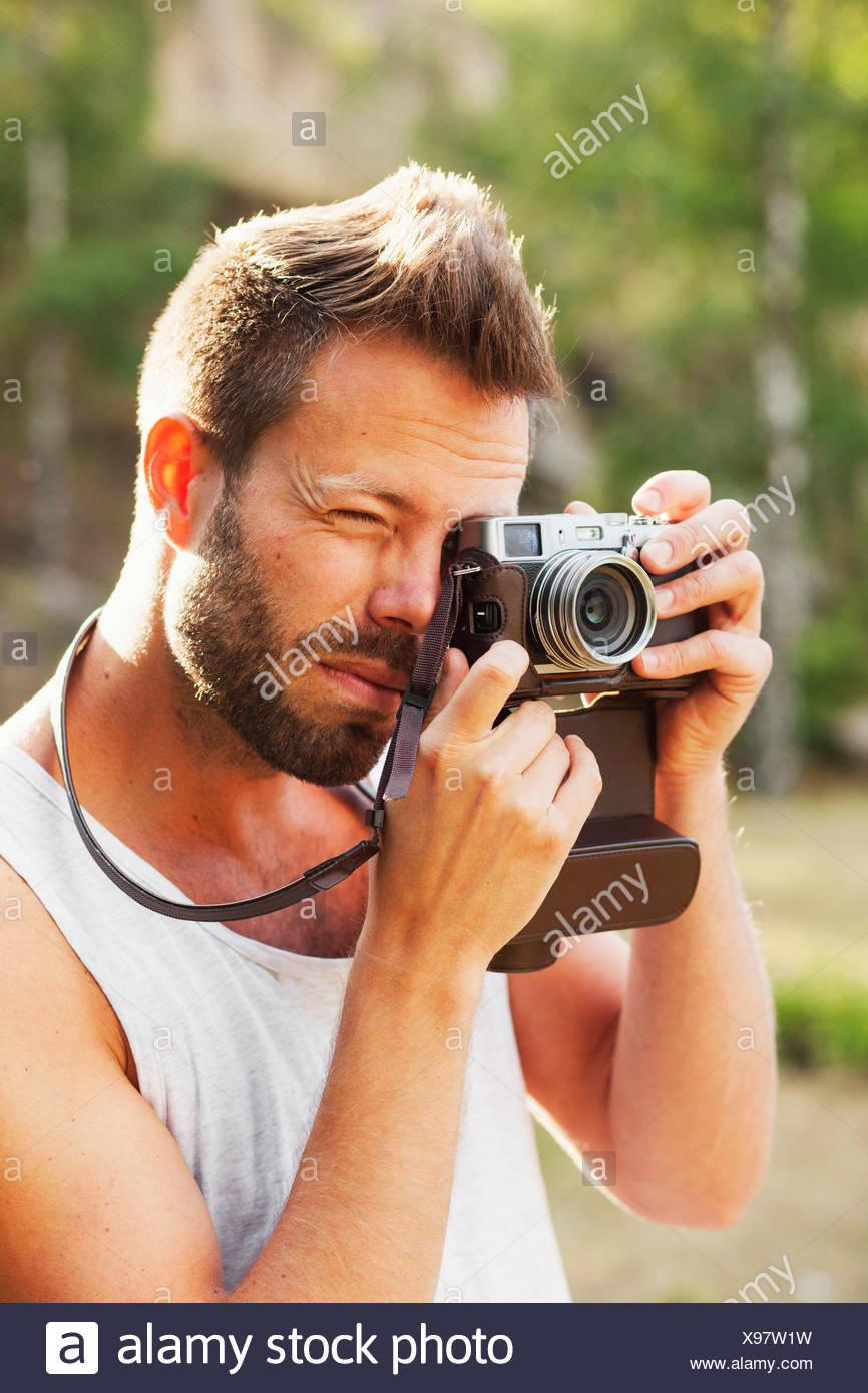 Mid adult man photographing through old-fashioned camera in forest - Stock Image
