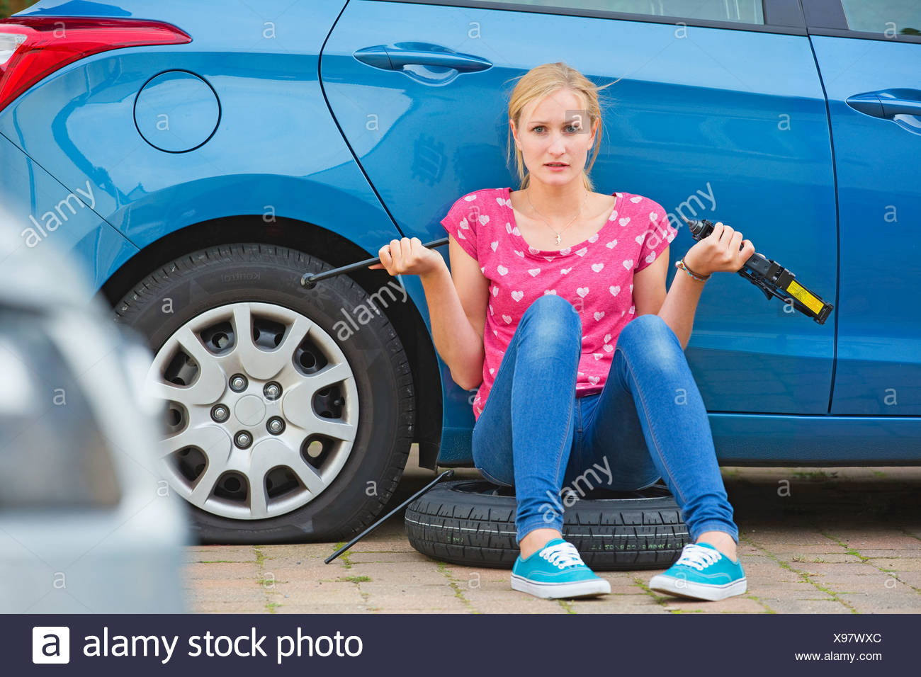 Frustrated Woman Trying To Change Flat Tyre On Car - Stock Image