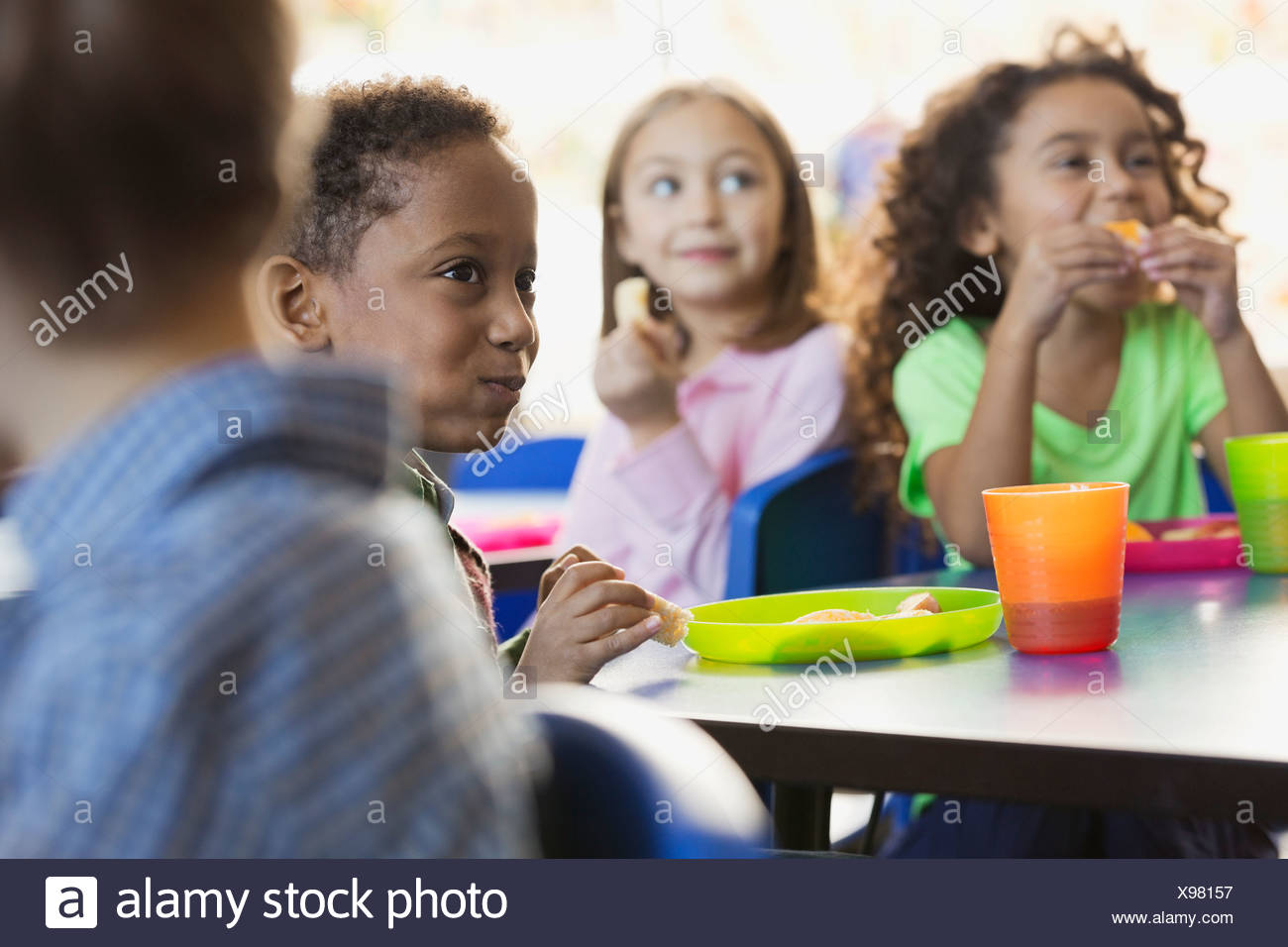 Children eating snacks in elementary school classroom - Stock Image
