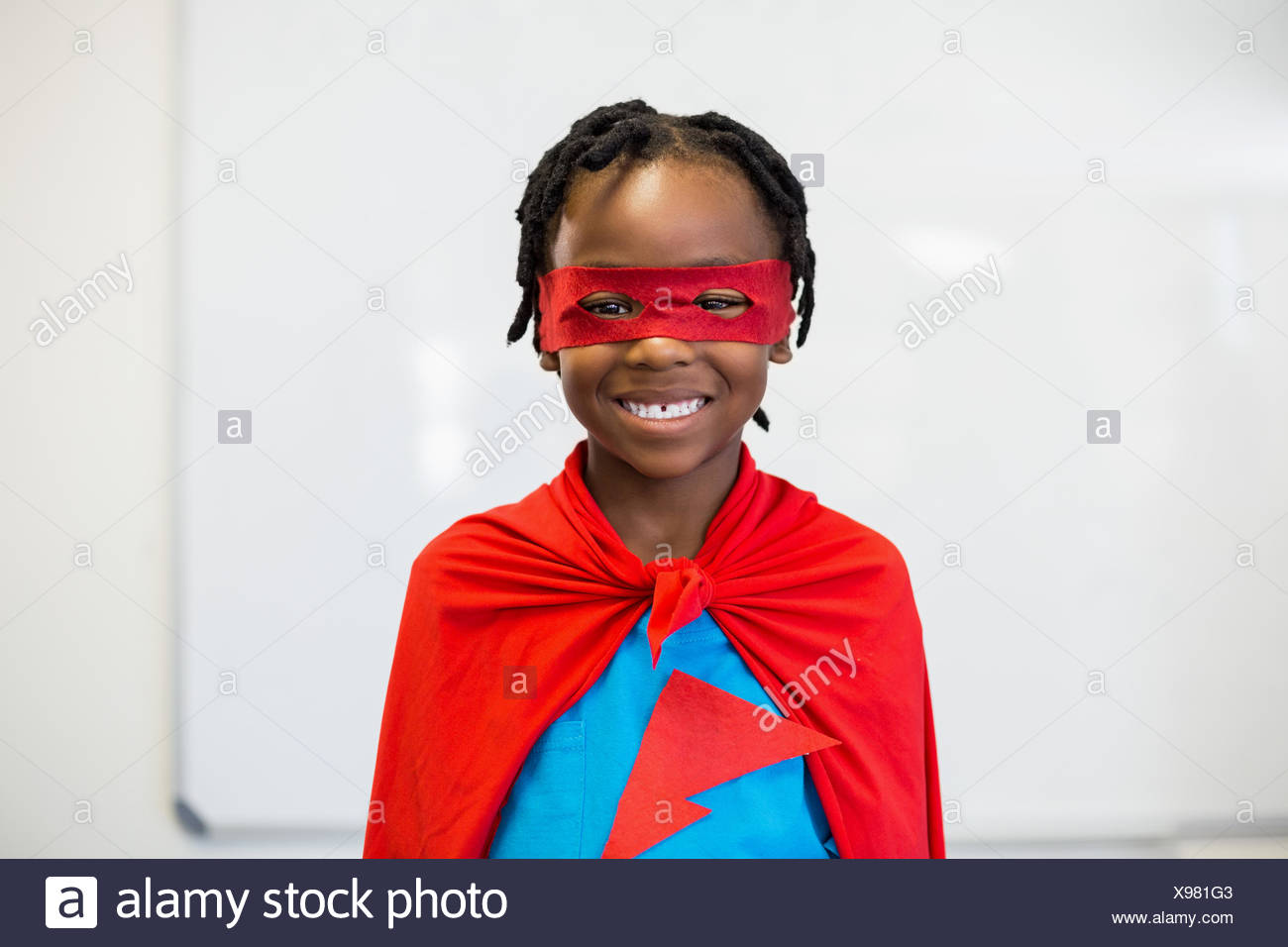 Smiling boy pretending to be a superhero - Stock Image