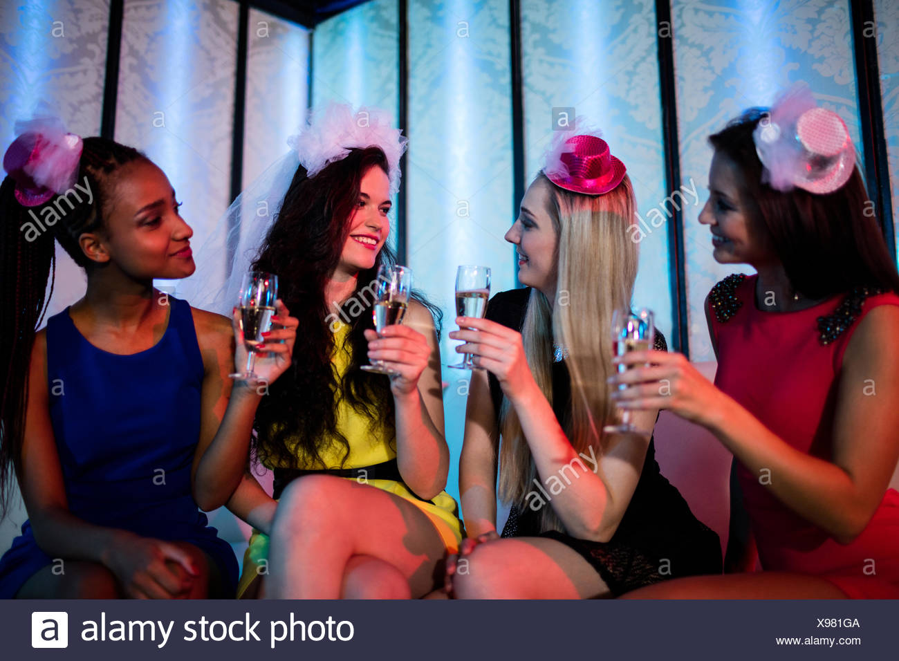 Group of smiling friend having glass of champagne - Stock Image
