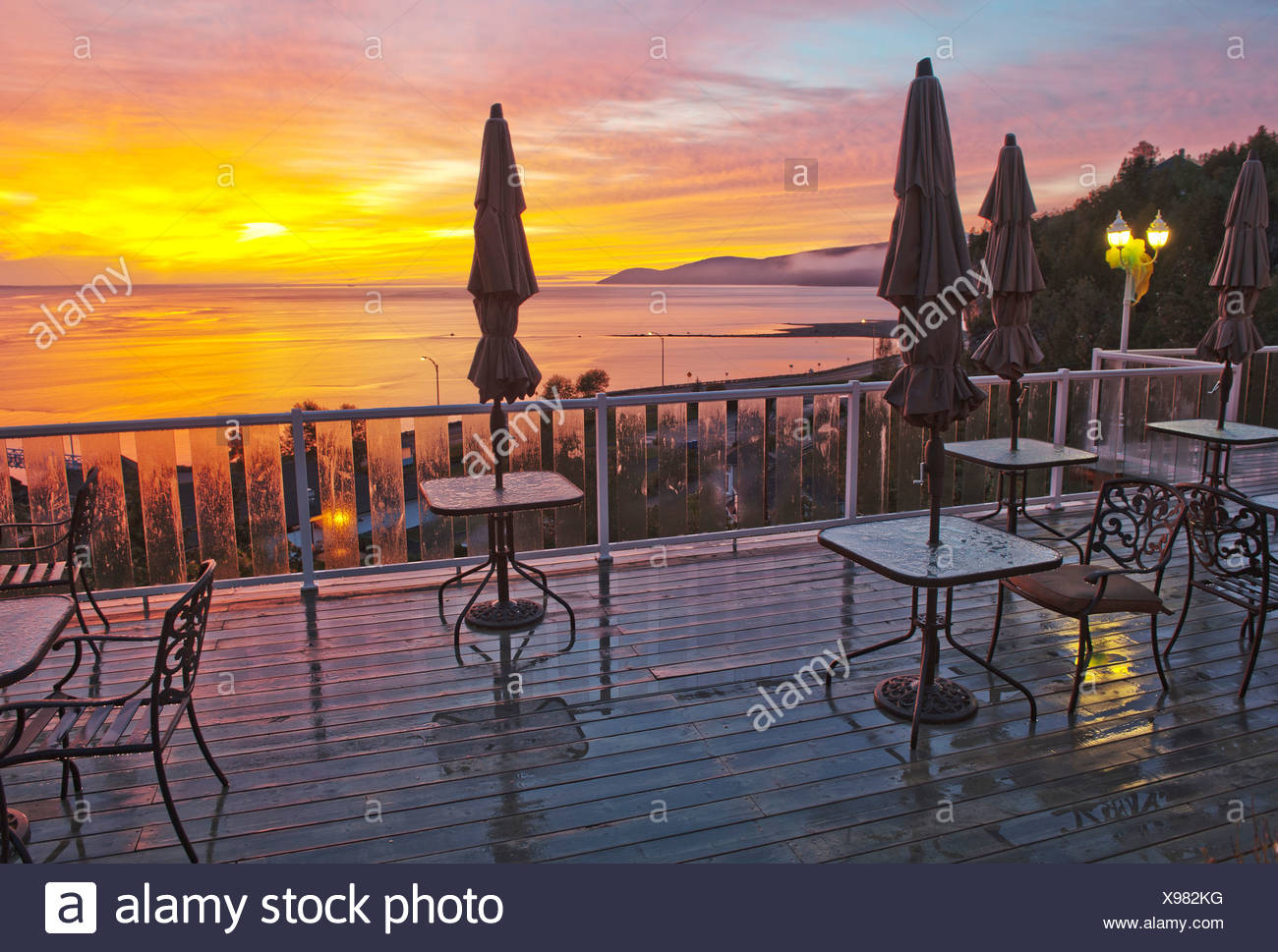 Terrace, Gite Mer et Montagne, St. Lawrence River, river, Malbaie, Quebec, Canada, sunset, tables, chairs - Stock Image