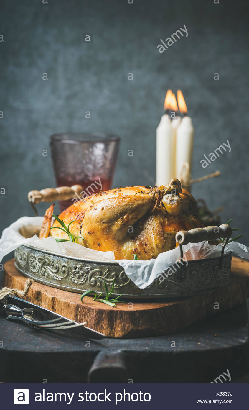 Christmas table set with roasted whole chicken with oranges, bulgur and rosemary, decorative candles, glass of rose wine, grey concrete wall backgroun - Stock Image