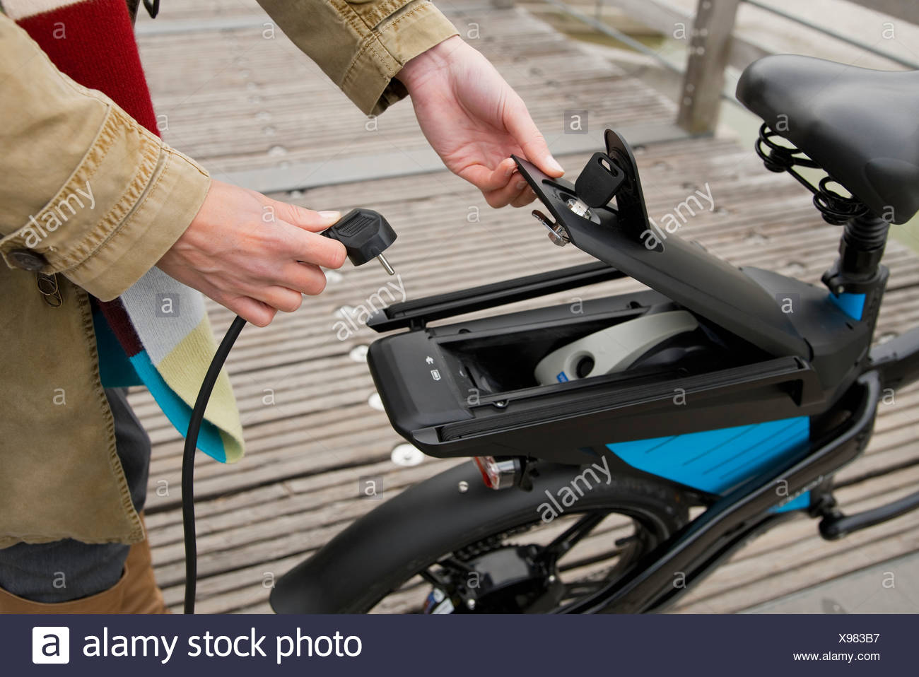 Woman charging electric bike outdoors - Stock Image