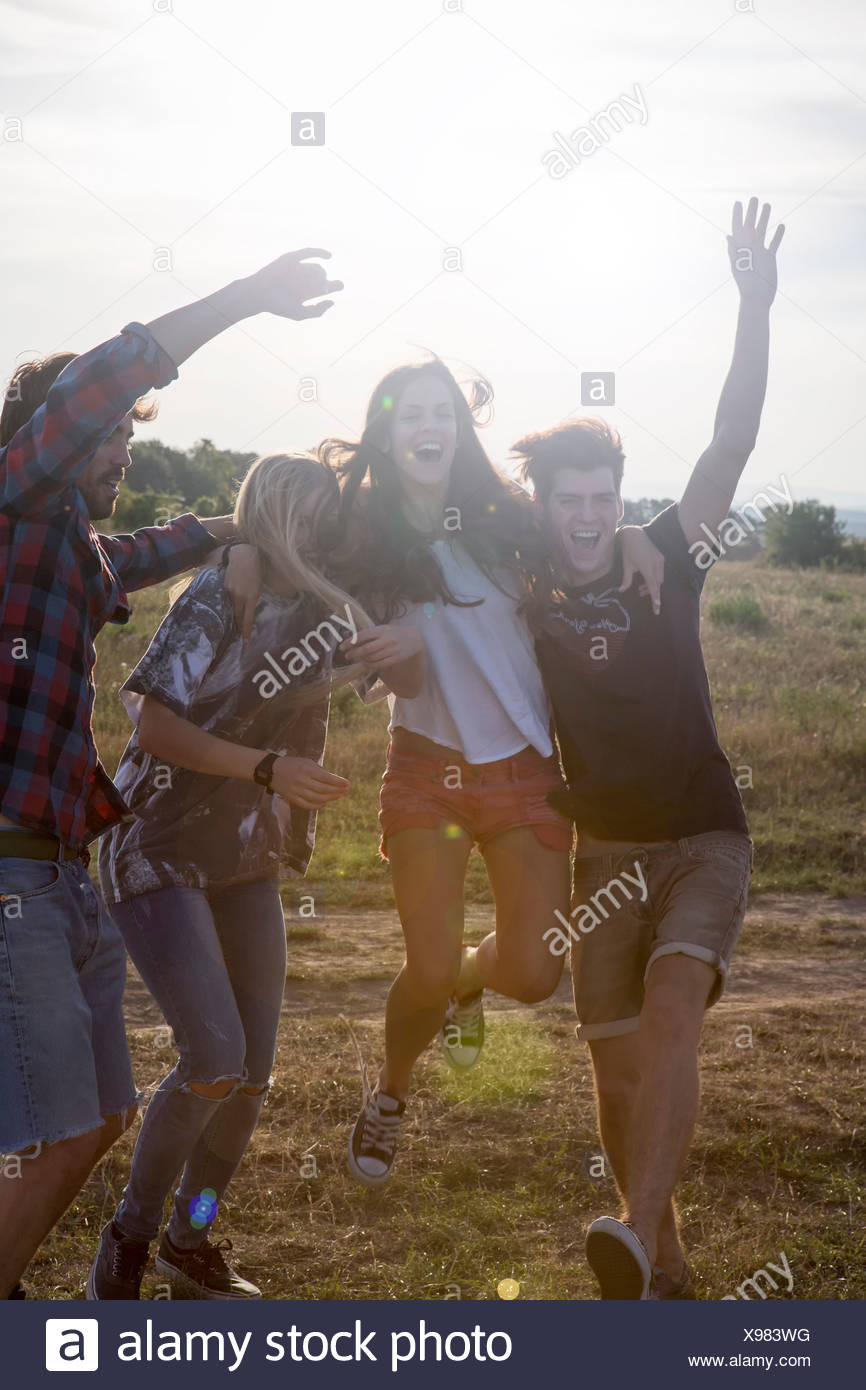 Four friends jumping with arms raised - Stock Image
