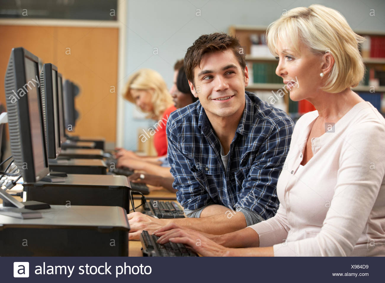 Students working on computers in library - Stock Image