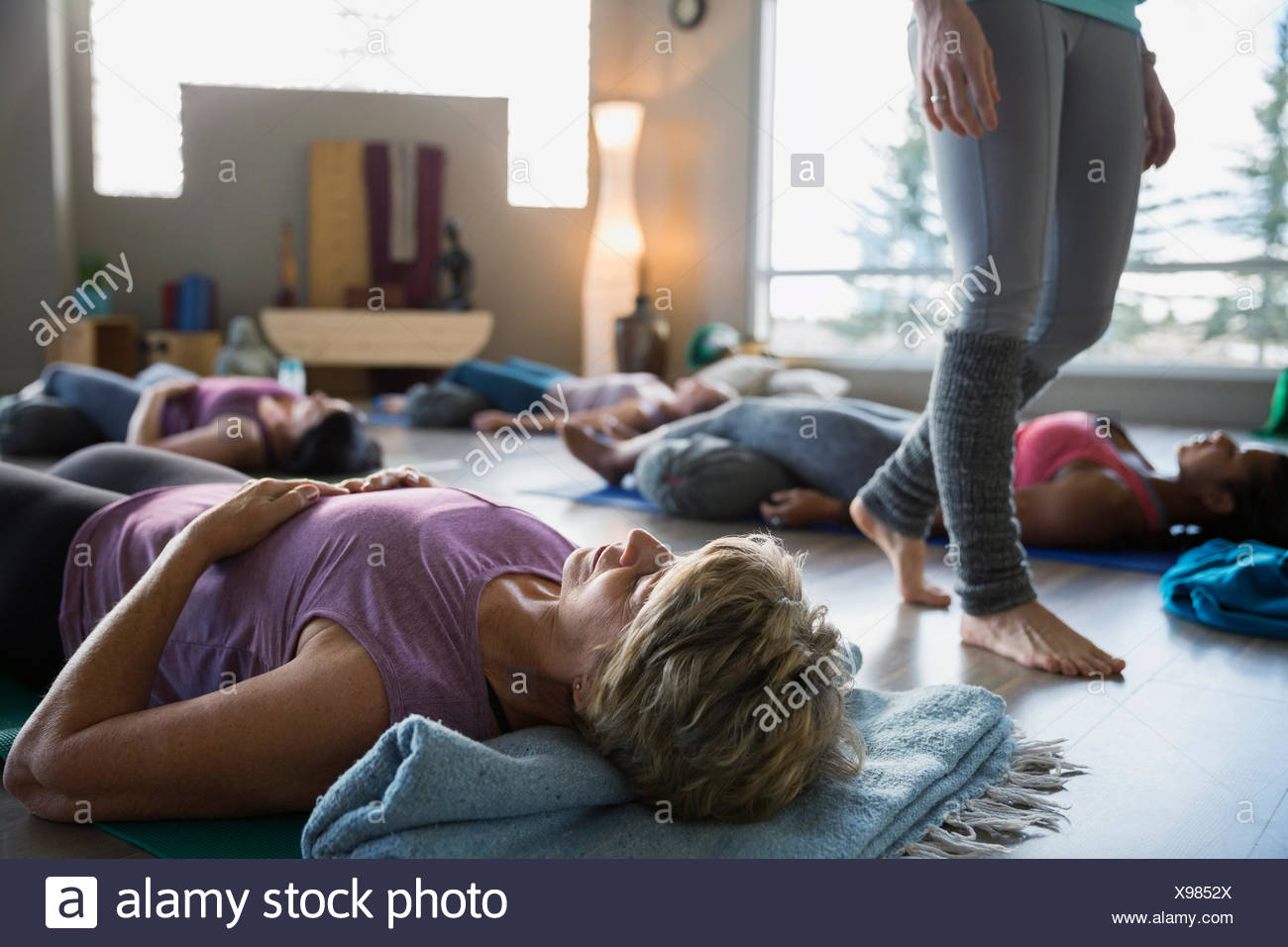 Women laying supported corpse pose in restorative yoga - Stock Image