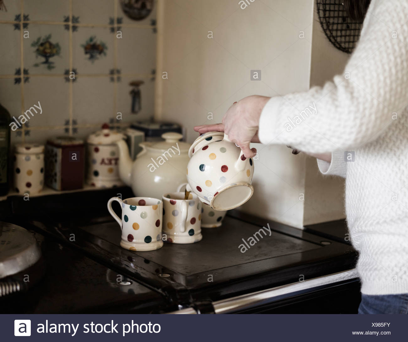 A woman pouring tea by a range cooker. Using decorative china. - Stock Image