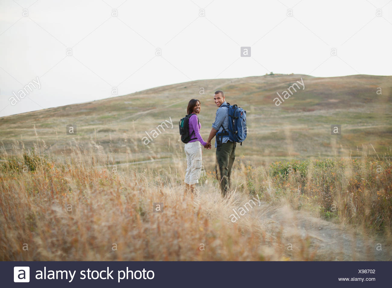Couple holding hands as they walk through a field. Stock Photo