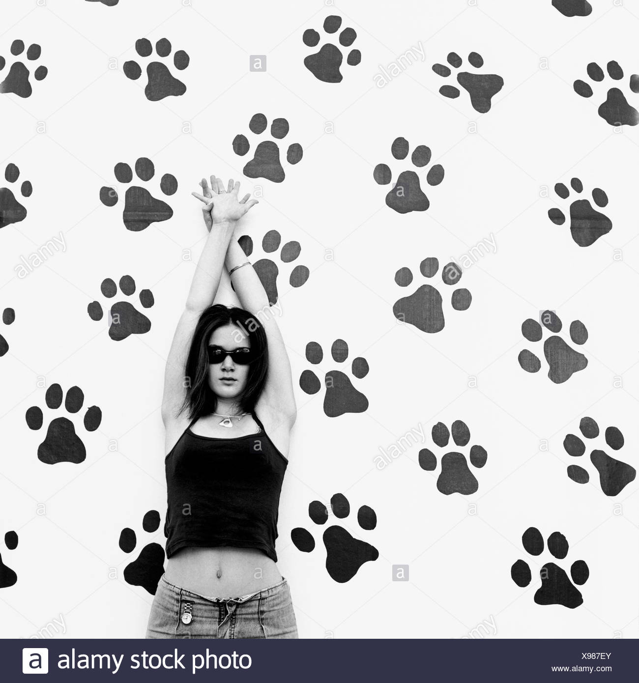 A teenage girl standing in front of a wall covered in black paw prints - Stock Image
