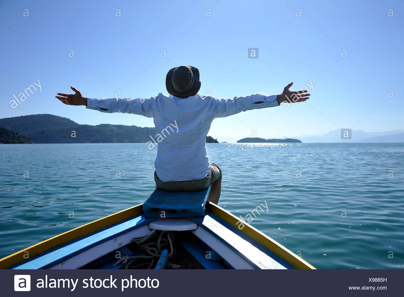 Young man sitting on the bow of a fishing boat with his arms wide open, Bay of Paraty or Parati, State of Rio de Janeiro, Brazil - Stock Image