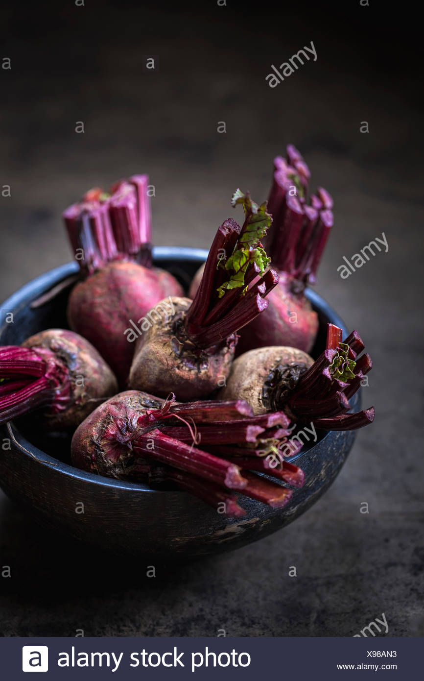 A bunch of red beets with their leaves cut off are in a dark wood bowl photographed from the front. - Stock Image