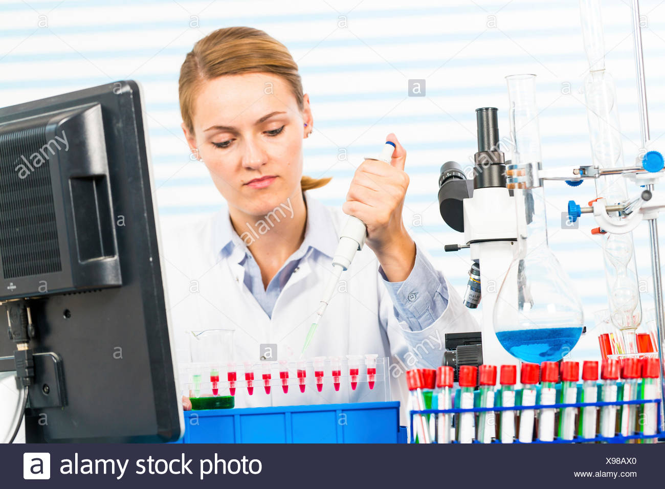 MODEL RELEASED. Female chemist using pipette in laboratory. - Stock Image