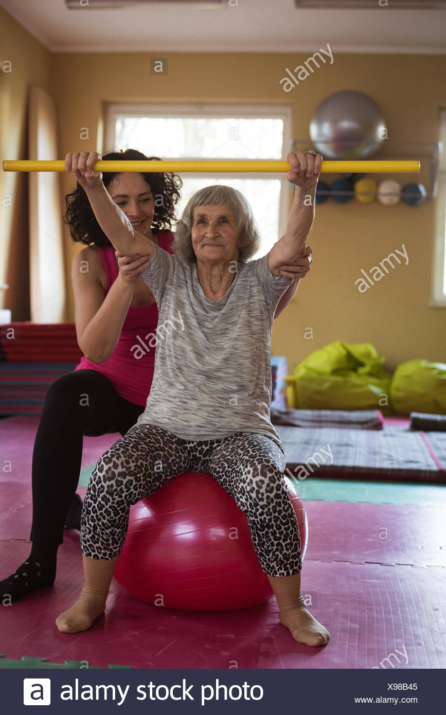Female therapist assisting senior woman with exercise stick and exercise ball - Stock Image