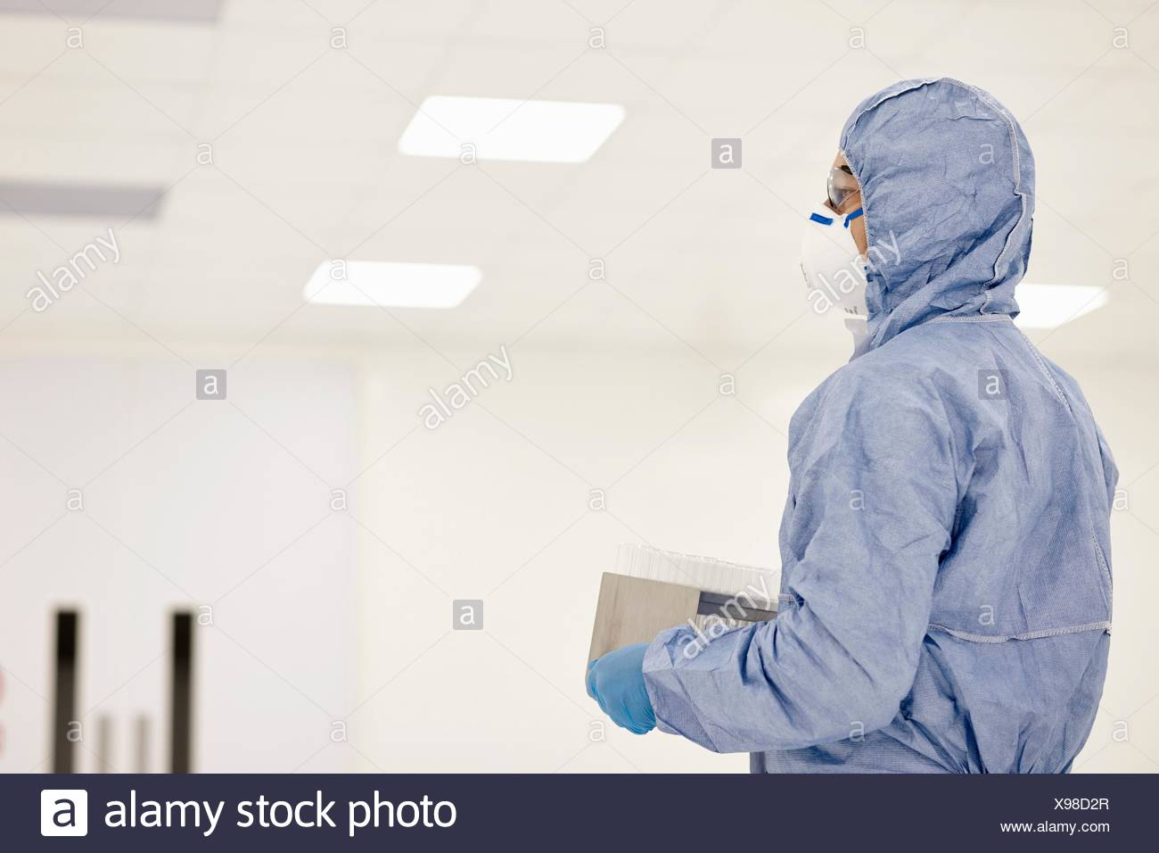 Scientist carrying tray of test tubes in laboratory Stock Photo