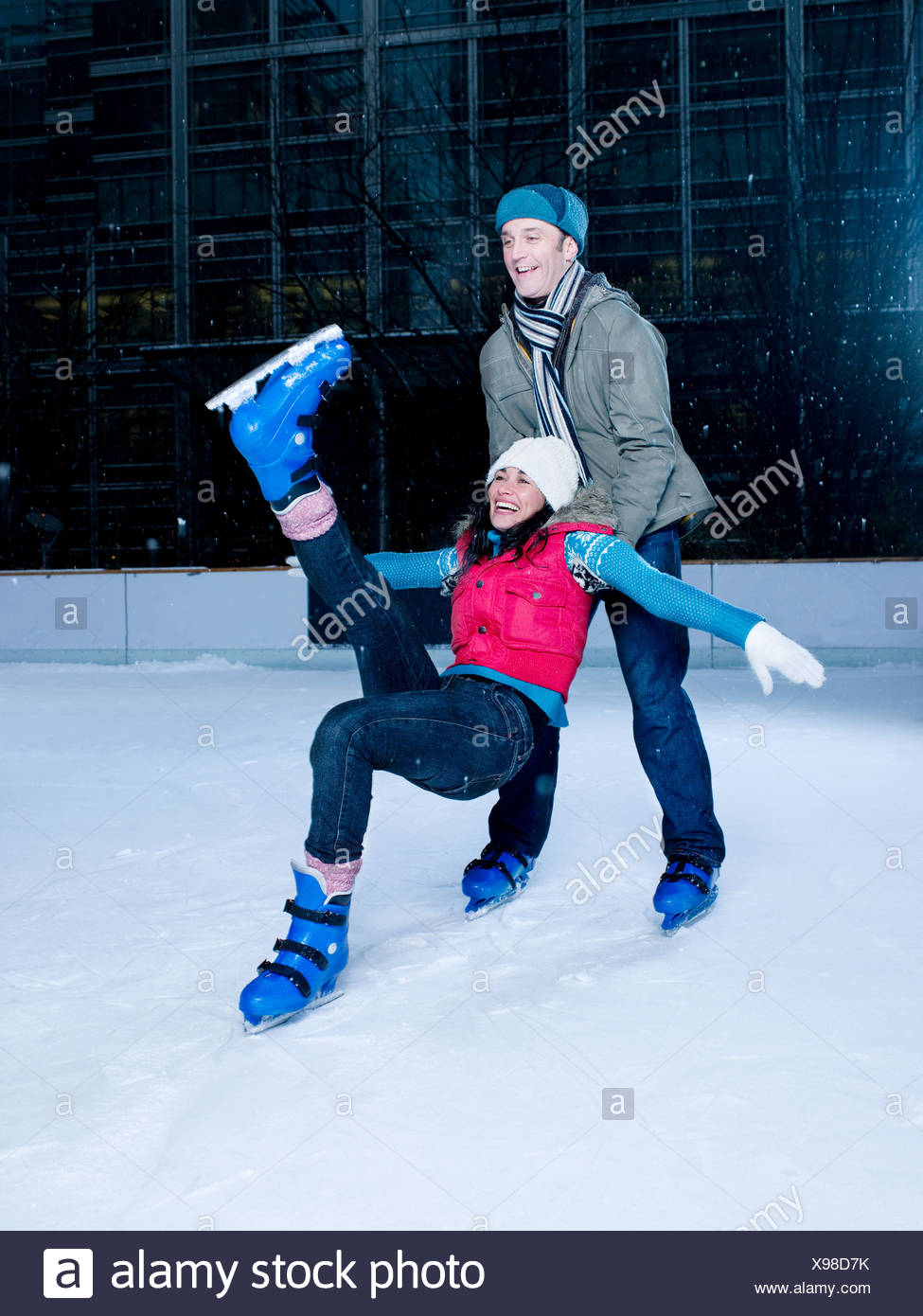 Man supporting woman as she falls while iceskating - Stock Image