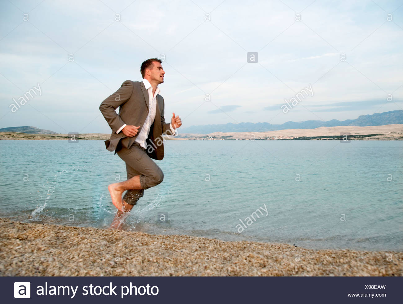 Businessman running on the beach Stock Photo