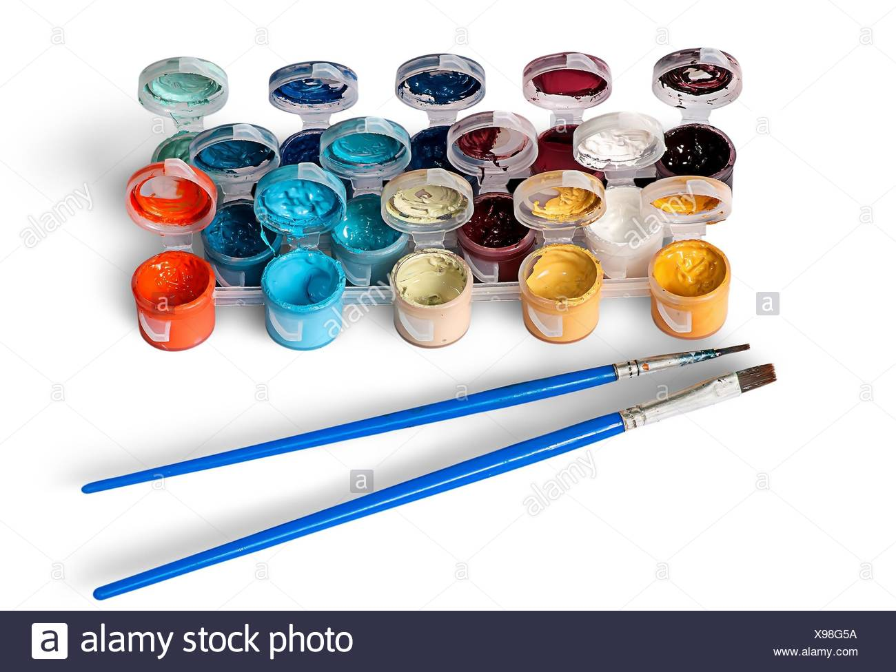 Set of colorful acrylic paints in jars and two brushes isolated on white background. - Stock Image