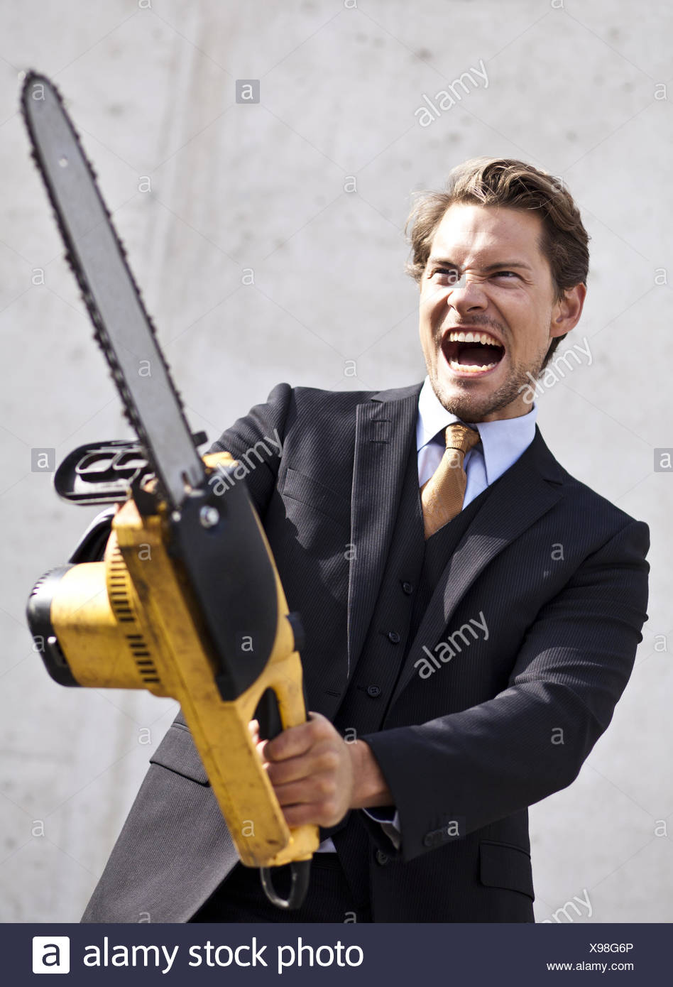 Angry businessman with blurred chainsaw - Stock Image