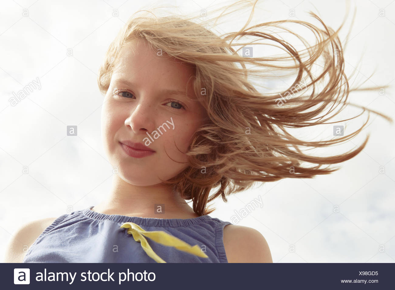 Portrait of girl with flyaway hair at breezy coast - Stock Image