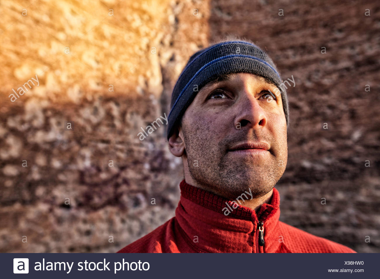 Portrait of rock climber looking up at rocks, Colorado, America, USA - Stock Image