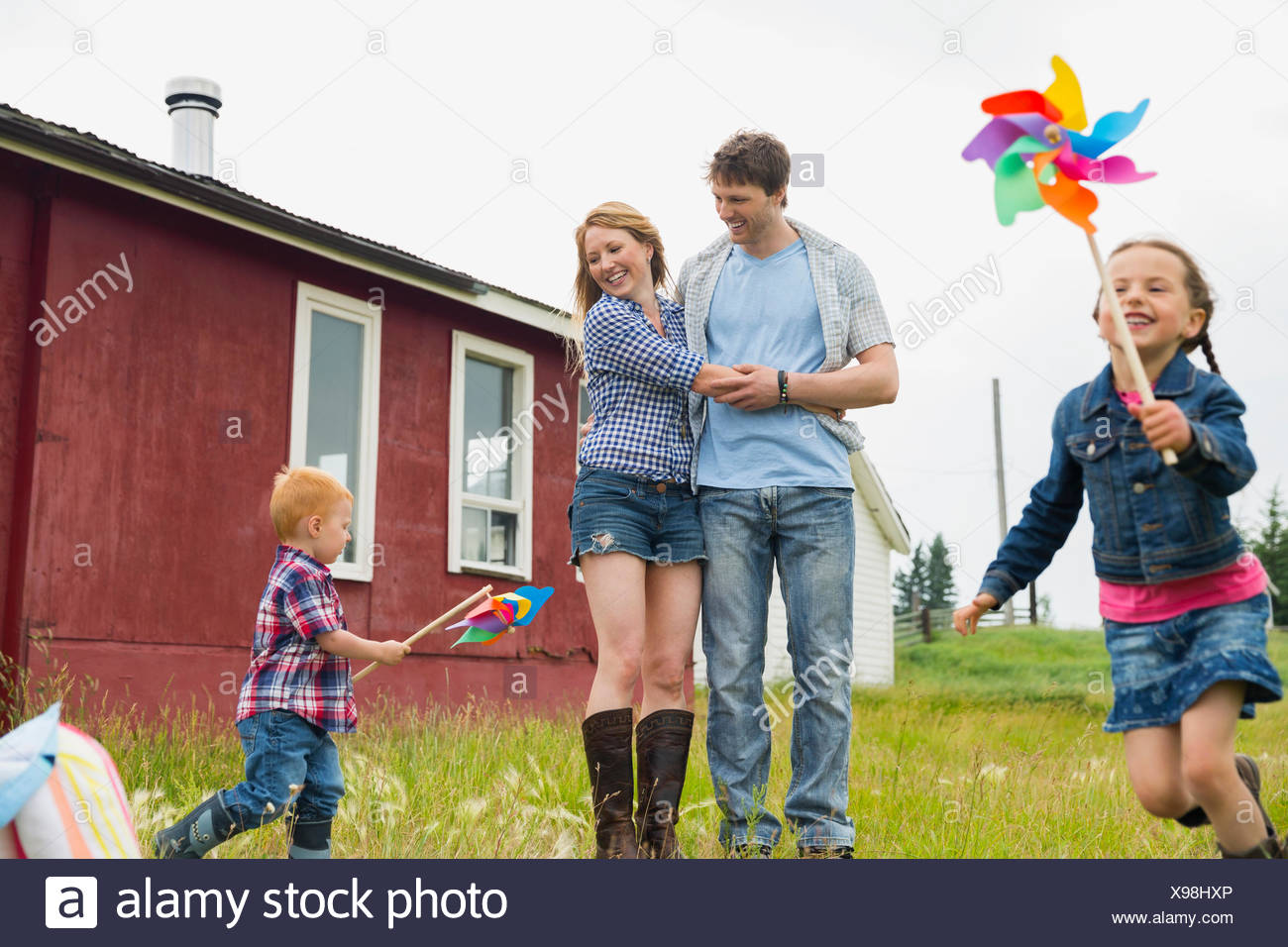 Parents watching children play with pinwheels - Stock Image