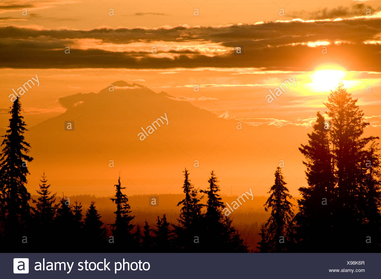 A setting sun silhouettes Redoubt Volcano across Cook Inlet as seen from the Kenai Peninsula in Southcentral Alaska, Summer - Stock Image