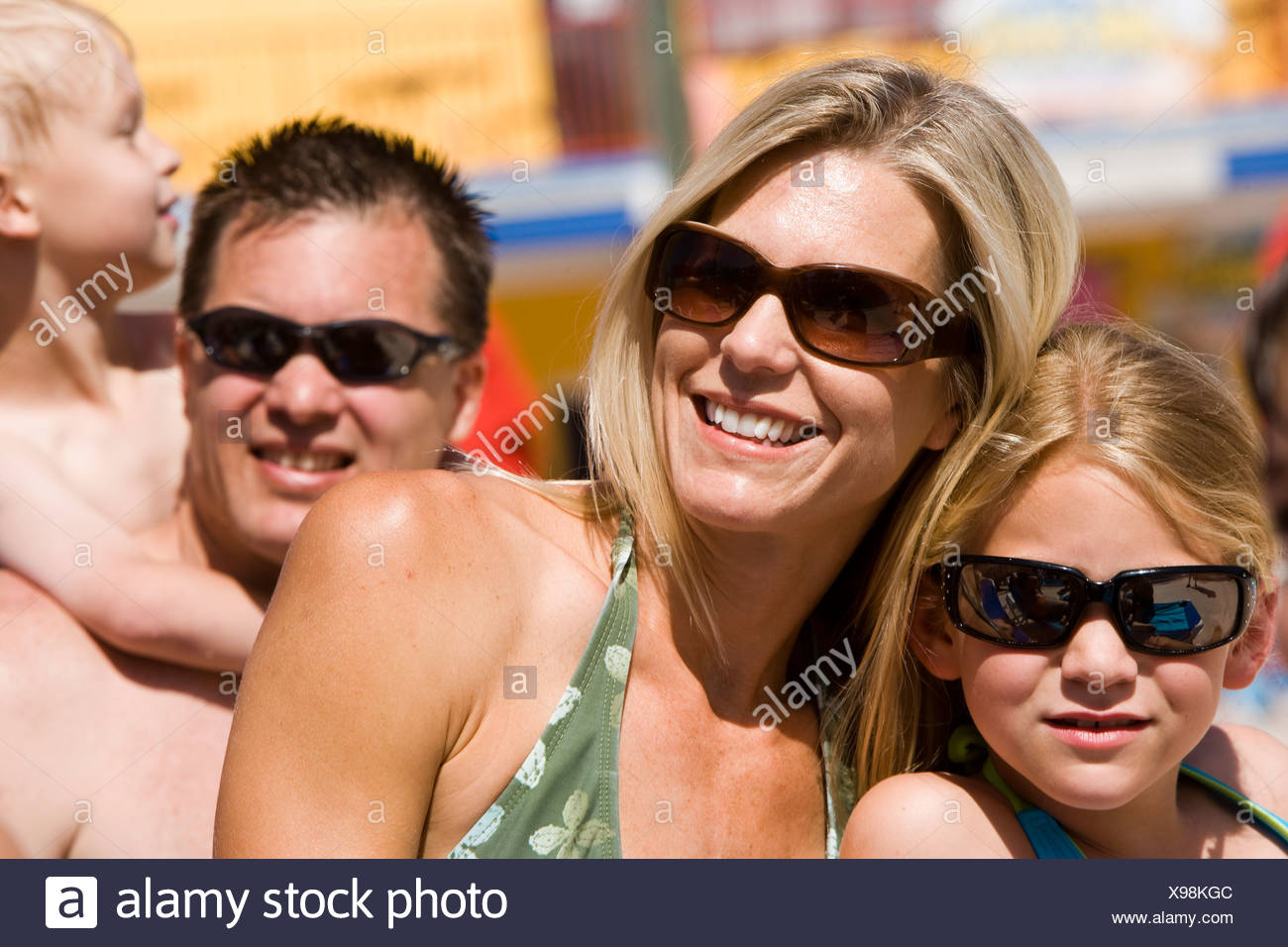 Headshot of family wearing swimsuits and sunglasses on sunny day - Stock Image