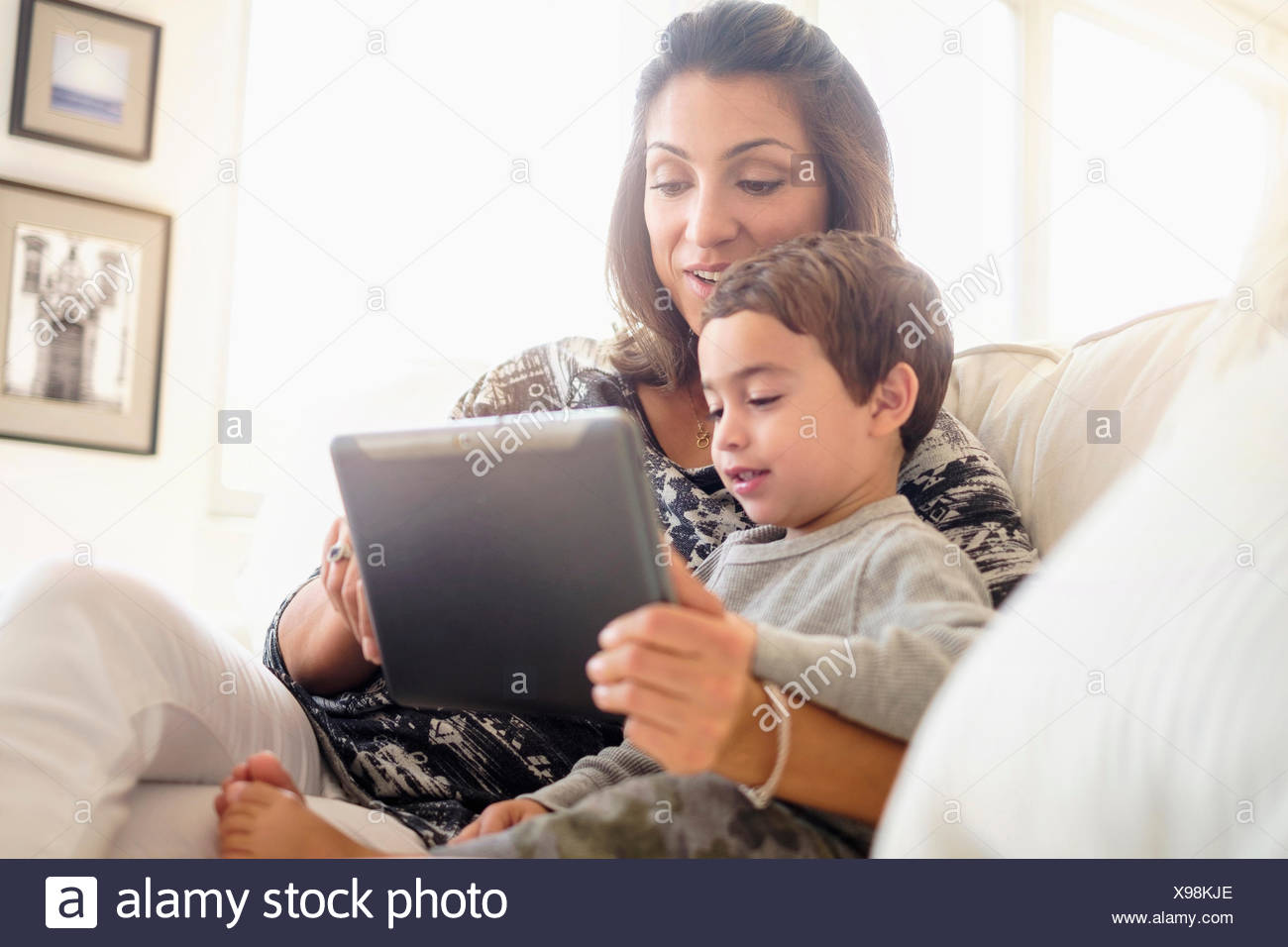 Mother reading with son (2-3) on sofa - Stock Image