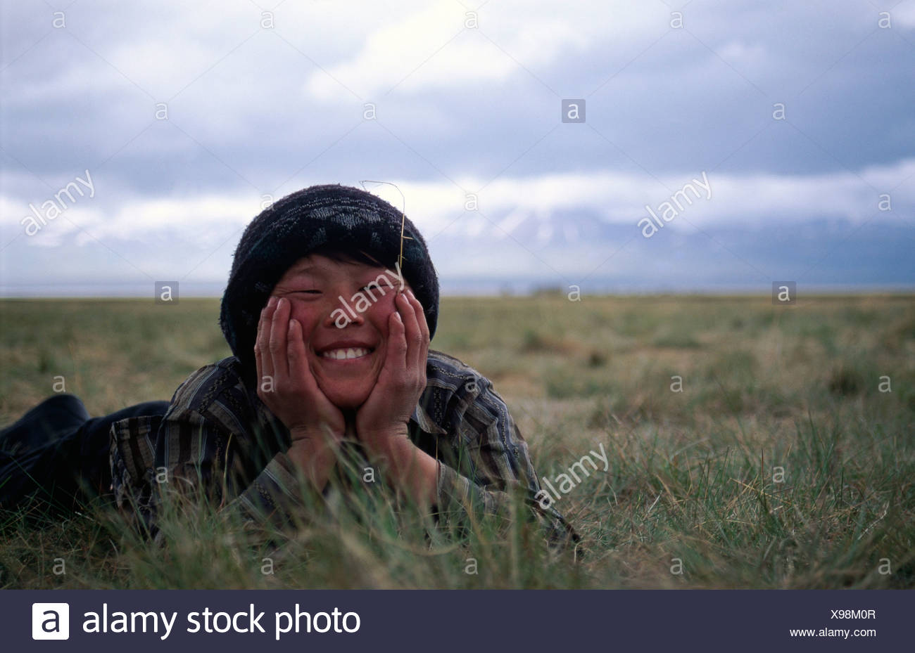 Nomad boy lying in the grass, Song-Kul, Kyrgyzstan, Central Asia - Stock Image