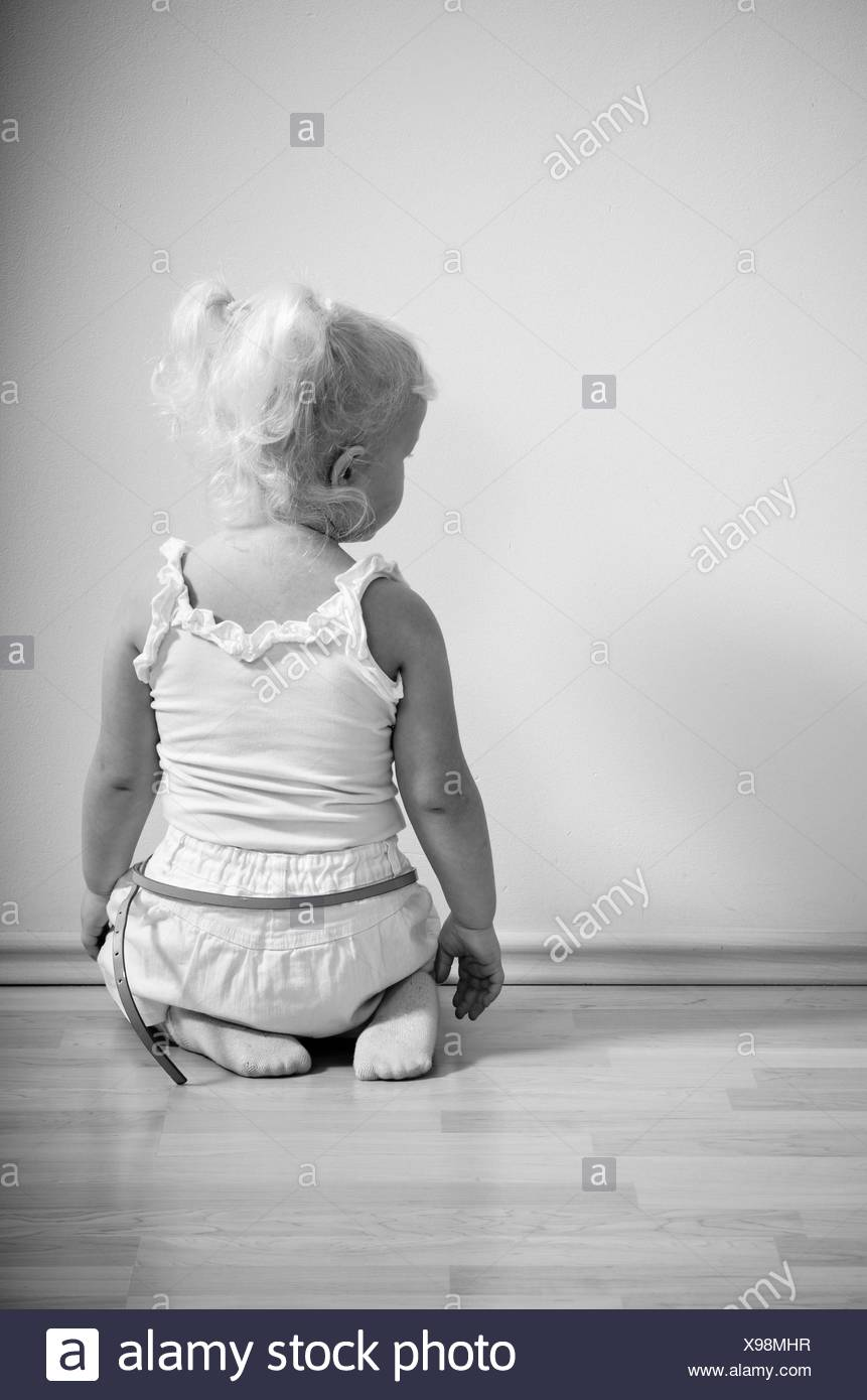 little girl sits on her knees facing the wall - Stock Image