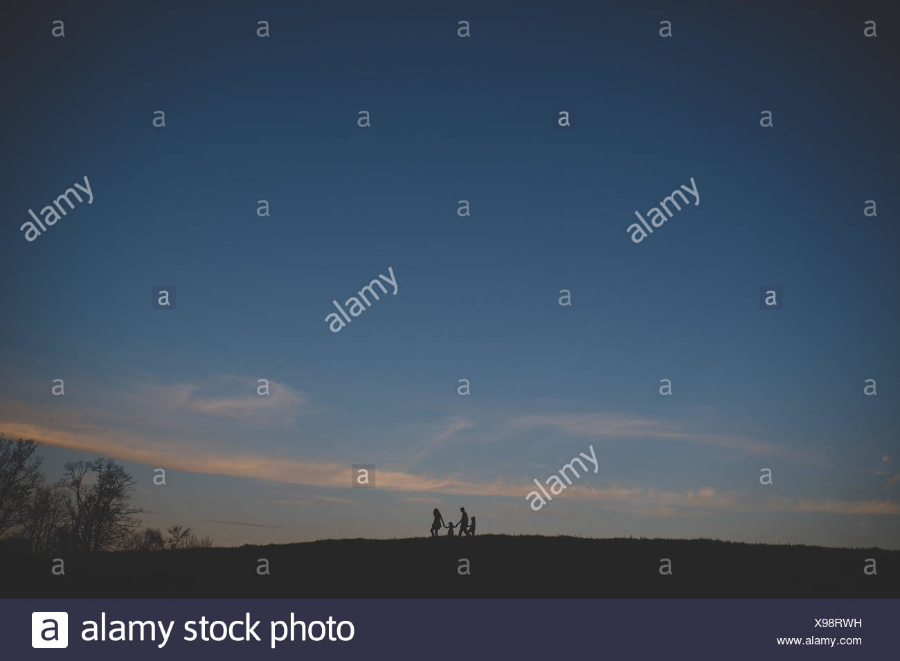 Silhouetted view of parents with son and daughter strolling on hill at dusk - Stock Image
