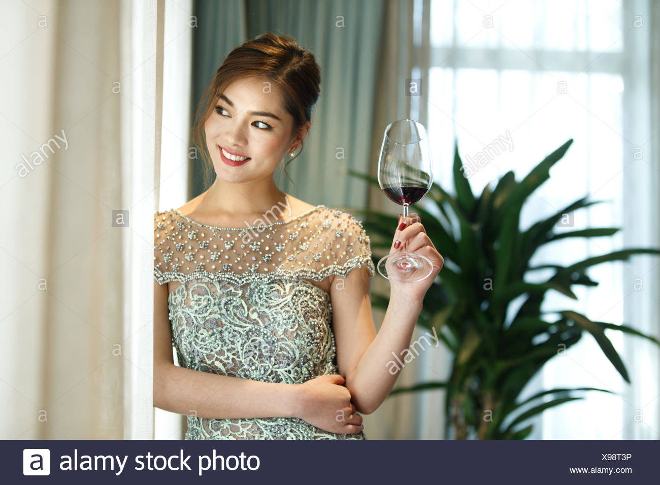 A beautiful young woman holding goblet - Stock Image