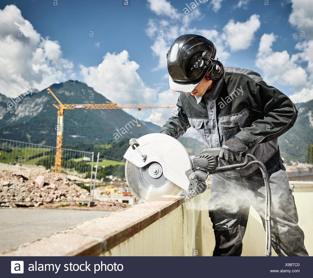 Construction worker with helmet, work clothes and ear protection cutting concrete wall with hand saw, Austria - Stock Image