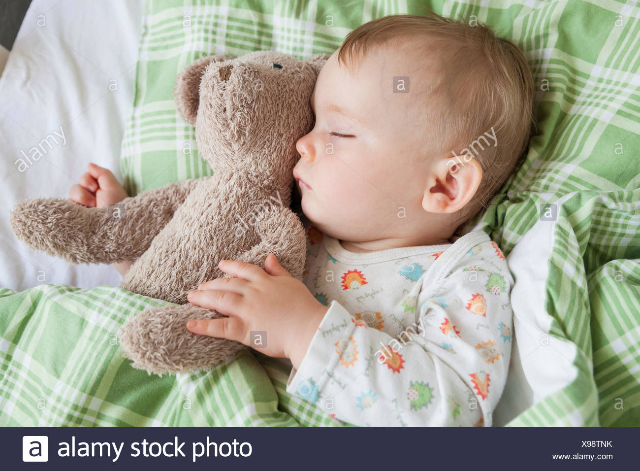 bbe3b3d40 Overhead view of baby boy asleep on bed holding teddy bear - Stock Image