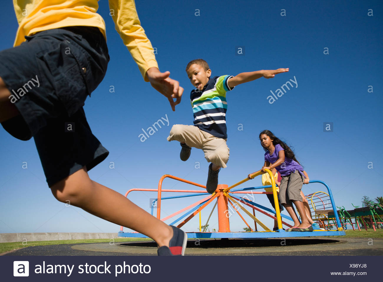 Children jumping off merry-go-round at playground - Stock Image