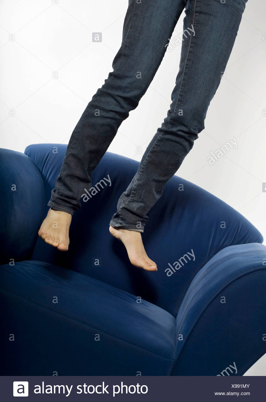 Woman in jeans jumping barefooted on a blue armchair - Stock Image
